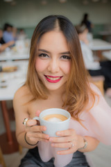 beautiful woman smile and holding a cup of coffee in her hand on blur background coffee shop