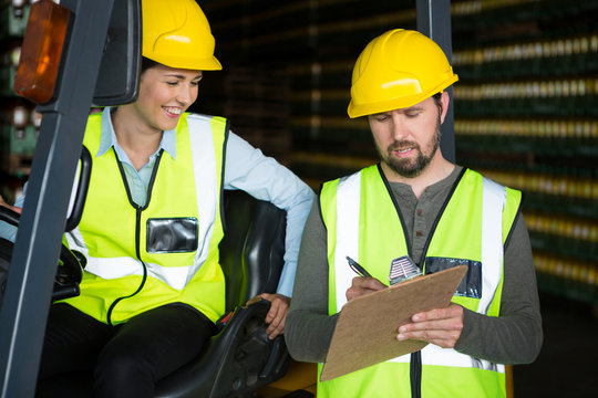 Smiling female worker with male worker at warehouse