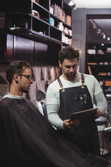 Barber showing hairstyle to client on digital tablet