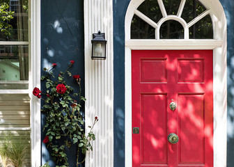 Lovely house facade with red door and roses in Notting Hill, London