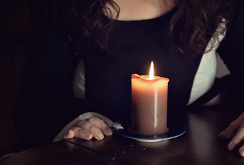 Faceless woman portrait sitting behind orange lit candle, closeup