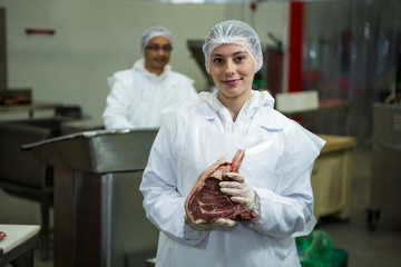 Female butcher holding meat at meat factory