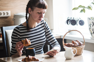 The girl is eating coffee with a croissant and checks the messages in the smartphone