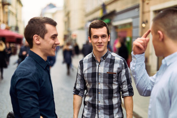 Three man talk on the street about business