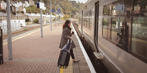 Woman getting in the train with luggage
