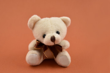Teddy bear toy stock images. Teddy bear on a brown background. Brown teddy bear with ribbon