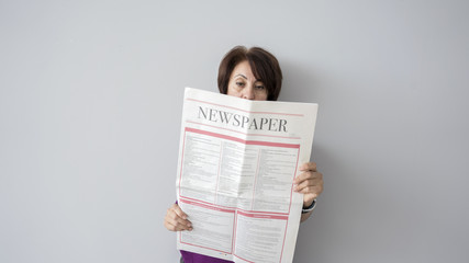Woman reading the newspaper on wall