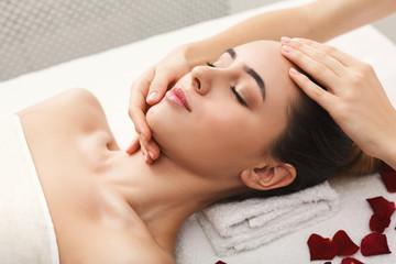 Woman getting professional facial massage at spa