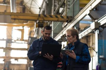 Technicians discussing over laptop