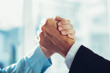 Close-up of two clasped hands of businessmen as sign of strong partnership or team. Unrecognizable men in arm wrestling gesture. Business union concept Wall mural