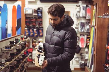 Man selecting ski binding in a shop