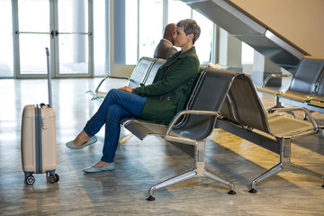Woman sitting with luggage at waiting area