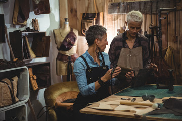 Craftswomen discussing over leather bag