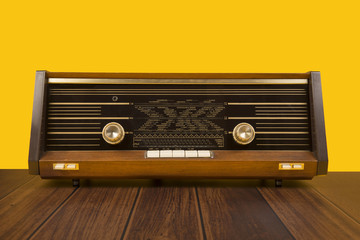 Old antique radio on a yellow background with dark brown wooden table