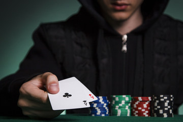 A guy in a black jacket holds a pair of aces against a pile of poker chips