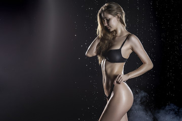 Beautiful wet blonde tall slim girl wearing a black lingerie posing in rain water drops in a studio on black background in a theatrical smoke