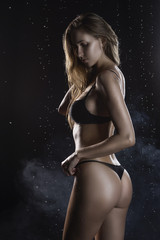 Beautiful wet blonde tall slim girl wearing a black lingerie poses from the back in rain water drops in a studio on black background in a theatrical smoke