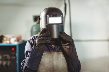 Welder holding welding helmet