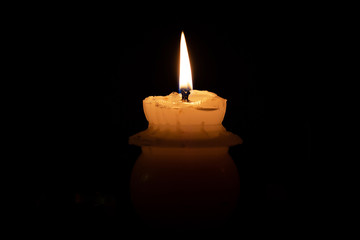 A memorial candle on a black background
