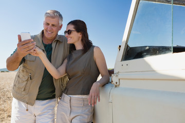 Couple looking into mobile phone by vehicle