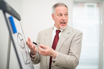Businessman showing data on a whiteboard