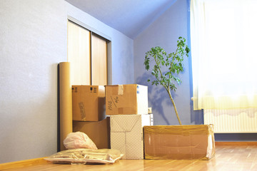 Old stacked cardboard boxes on light brown floor in blue  empty room. Moving boxes in new house with copy space for text.