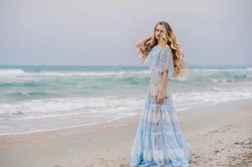 Beautiful girl in amazing dress walks on the beach