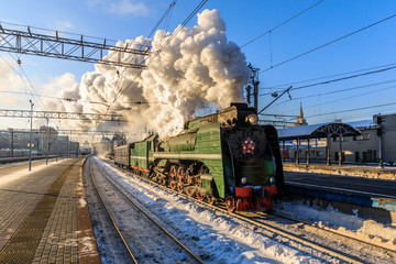 old black steam locomotive in Russia in the winter on the background of the Moscow railway station