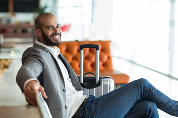 Portrait of smiling businessman sitting on chair in waiting area