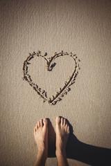 Woman standing near heart drawn on the beach