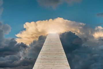 Wooden staircase as footpath is leading to bright and cloudy sky. Concept of success, achievement, development, promotion or career.