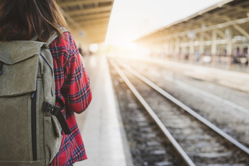 Young Asian woman backpacker traveler walking alone at train station platform with backpack. Asian woman waiting train at train station for travel. Summer holiday traveling or young tourist concept.