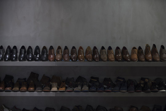 Shelves with brown and black mens shoes. Row of leather mens shoes. Mens shoes, boot sell in store, boutique, shopping mall. Mens shoes concept. Mens fashion, style, quality, leather, leatherette.