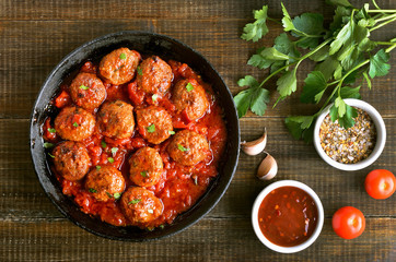 Meatballs in cast iron pan, fresh parsley and tomatoes