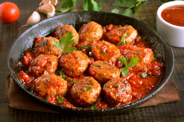 Meatballs with parsley in cast iron pan