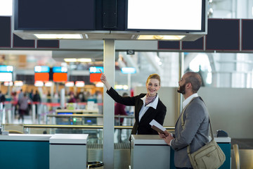 Airline check-in attendant showing direction to commuter at check-in counter