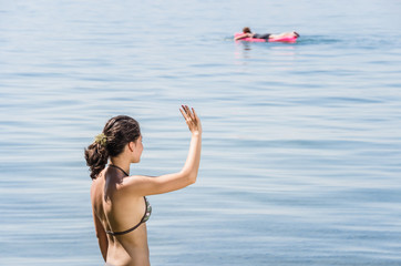 Portrait of young women waving to another person on air mattress in Lake Constance