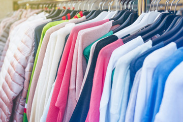Colorful woman's clothes on black hangers in cloth's shop.