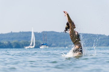 Portrait of young women jumping in Lake Constance with sailing boats in the background