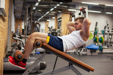 sport, fitness, bodybuilding, lifestyle and people concept - young man doing sit-up abdominal exercises Bench Press in gym