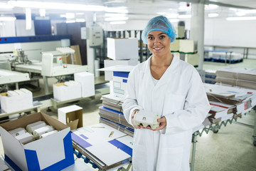 Portrait of female staff holding carton of eggs