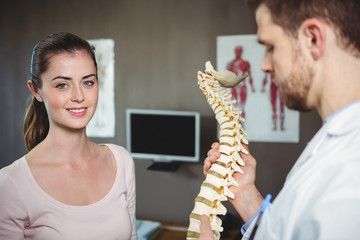 Physiotherapist holding spine model while patient smiling at camera