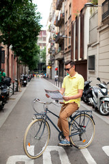 Hipster man riding vintage bike and reading map in tourist area in european city