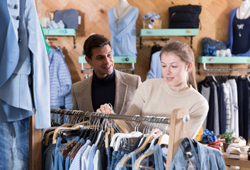 Young female with male are looking on jeans clothes on hanger