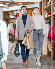 Young woman and man are walking satisfied with packadge after shopping