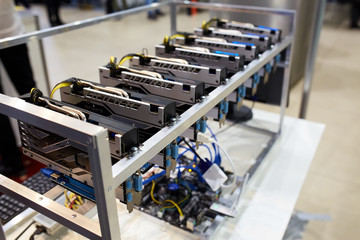 Crypto currency ethereum mining equipment rig - lots of gpu cards on mainboard. Graphics processing units connected to motherboard with cables. Server with decryption and encryption computing machines