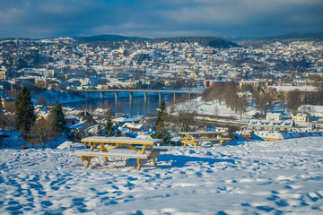 Beautiful outdoor view of wooden chair and the norwegian city Trondheim in the horizont in the winter