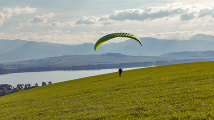 Paraglider starts flight from the hill. Extreme sports activity.