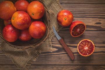 Blood orange fruit in a wicker basket and bottle juice