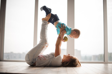 Mother, lying on the floor, holding her little son up in the air